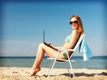 Girl looking at tablet pc on the beach Royalty Free Stock Photography