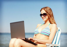 Girl looking at tablet pc on the beach Stock Photos