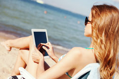 Girl looking at tablet pc on the beach Stock Photo