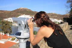 Girl looking through telescope. Girl exploring a village landscape with telescope Royalty Free Stock Photography