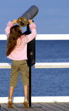 Girl looking through telescope. Girl standing on her toes trying to look through telescope onto the water Stock Image