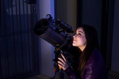Girl looking through a telescope Royalty Free Stock Images