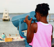Girl Looking Through Telescopic Viewer. A young girl views boats and scenery at the beach through a telescopic viewer Stock Photos