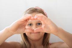 Girl looking thru heart Royalty Free Stock Image