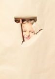 Girl looking thru hole royalty free stock image