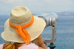 Girl looking thru public binoculars at the seaside wearing pink Royalty Free Stock Photo