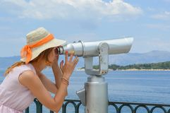 Girl looking thru public binoculars at the seaside wearing pink Stock Photos