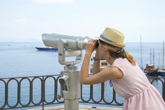 Girl looking thru public binoculars at the seaside wearing straw Royalty Free Stock Photography