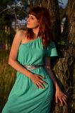 Girl looking to the side. Girl in blue looks away leaning against a tree Royalty Free Stock Photo