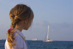Girl looking to the yacht. Little girl looking to the yacht in the ocean Royalty Free Stock Photo