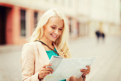 Girl looking into tourist map in the city Stock Photos