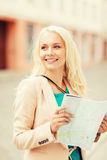 Girl looking into tourist map in the city Stock Photo