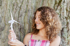 Girl Looking At Toy Windmill Against Tree Trunk Stock Image