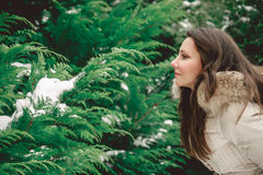Girl looking at tree. Girl in green forest looking at tree branch Stock Photo