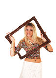 Girl looking trough picture frame. royalty free stock photography