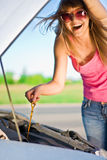 Girl looking under the car. Beautiful blonde girl looking under the hood of the car Stock Images