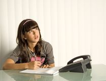 Girl Looking Up. Teenager sitting at desk looking up with phone Stock Photography