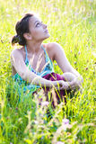 Girl looking up. Young woman sitting in a field of flowers looking up Royalty Free Stock Photo