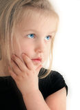 Girl looking up. Cute young girl with hand on chin, looking up with blue eyes Royalty Free Stock Photography