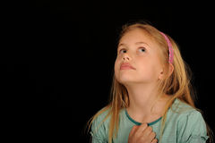 Girl looking up. Horizontal portrait of a young girl looking up and to her left, with her right hand in a fist against her chest.  Isolated against a black Royalty Free Stock Image