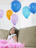 Girl Looking Up At Balloons On Sofa Royalty Free Stock Images