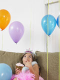 Girl Looking Up At Balloons On Sofa