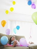 Girl Looking Up At Balloons On Sofa Royalty Free Stock Photos