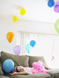 Girl Looking Up At Balloons On Sofa Stock Photo