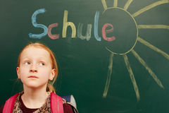 Girl looking up on the board. Little girl looking up on the chalkboard royalty free stock photography