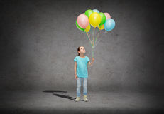 Girl looking up with bunch of helium balloons