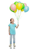 Girl looking up with bunch of helium balloons Royalty Free Stock Photos