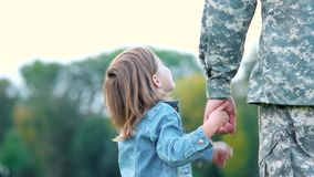 Girl looking up and pointing, holding hand of father. stock video footage