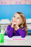 Girl Looking Up While Sitting With Head In Hands Stock Images