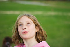 Girl looking up into the sky. Twelve year old girl outdoors looking up into the sky Stock Image