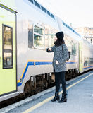 Girl looking up and standing next to a train Stock Images
