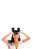 Girl looking upward through binocular. On an isolated white background Stock Images