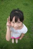 Girl looking upward with victory sign. Girl smiling & looking upward with victory hand sign stock images