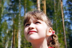 The girl looking upwards. In the summer on the nature the child looks upwards Stock Photo