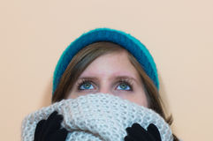 Girl looking upwards while she is wearing a fluffy scarf and a blue beanie Stock Photo