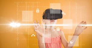 Girl looking at various icons through VR glasses. Digital composite of Girl looking at various icons through VR glasses Stock Images