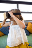 Girl looking through virtual reality in school library Royalty Free Stock Photos