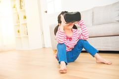 Girl looking in a VR goggles device. Amazed little asian cute girl looking in a VR goggles device and gesturing with hands seated on wooden floor in the living Stock Images