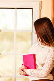 Girl looking through window holds book Royalty Free Stock Image