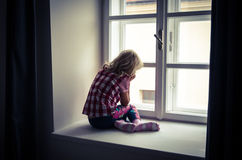 Girl looking through window. Little blond girl sitting and looking over window Royalty Free Stock Photography
