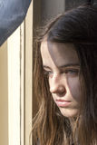 Girl looking through a window Royalty Free Stock Image