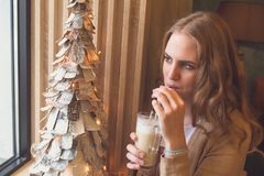 Girl looking in window and sitting in cafe and drink latte coffee, Christmas decoration. stock photography