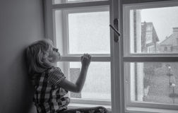 Girl looking through window Stock Photo