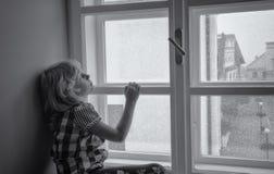 Girl looking through window. Small girl alone looking through window how it is snowing outside Stock Photo