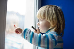 Girl looking through the window Royalty Free Stock Photo