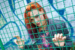 Girl looking through wire fence Stock Images